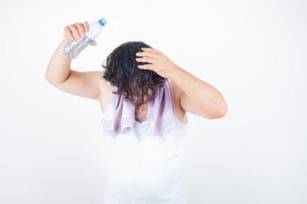 Homme d'âge moyen en débardeur, serviette versant de l'eau sur la tête avec une bouteille et à la drôle, vue de face.
