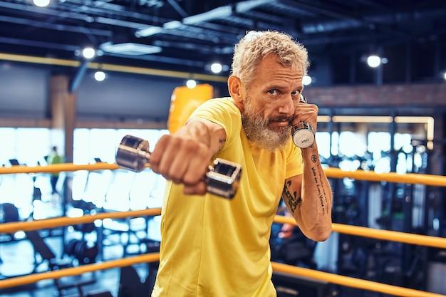 Homme d'âge moyen debout sur le ring et boxe avec haltère et regardant la caméra tout en travaillant