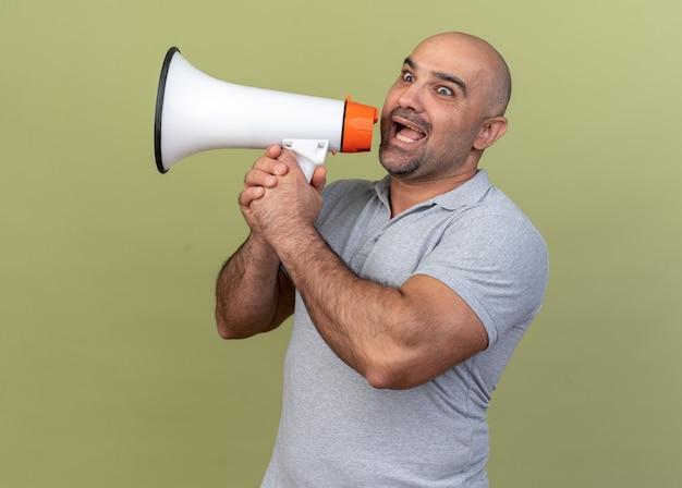 Homme d'âge moyen décontracté impressionné regardant le côté parlant par le haut-parleur isolé sur un mur vert olive
