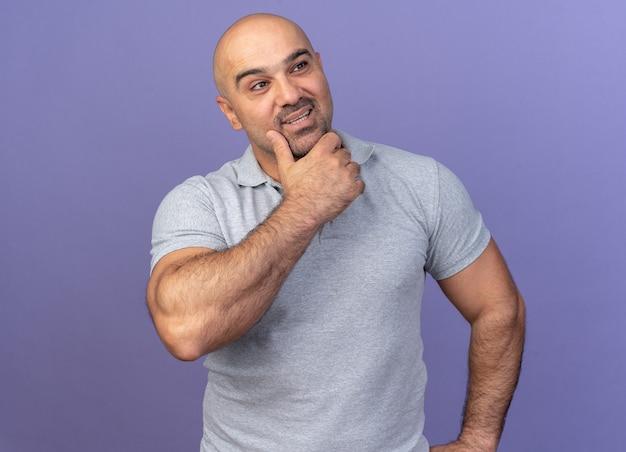 Homme d'âge moyen décontracté et réfléchi, gardant la main sur le menton en regardant le côté isolé sur le mur violet