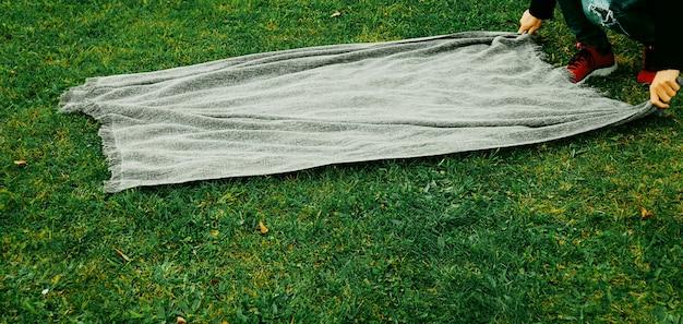 Homme d'âge moyen dépliant une couverture dans le parc. notion de santé mentale. isolement, solitude, temps seul, rituels et concept de distanciation sociale