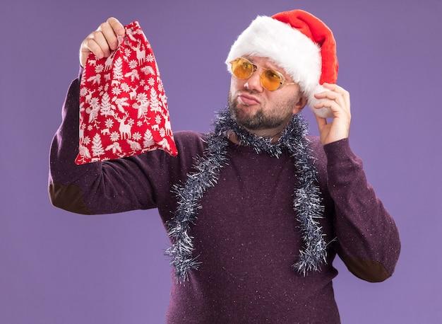 Homme d'âge moyen douteux portant un chapeau de père noël et une guirlande de guirlandes autour du cou avec des lunettes tenant et regardant un sac de cadeau de noël attrapant un chapeau isolé sur fond violet