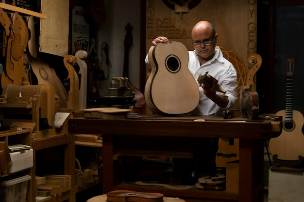 Homme d'âge moyen fabriquant des instruments dans son atelier seul