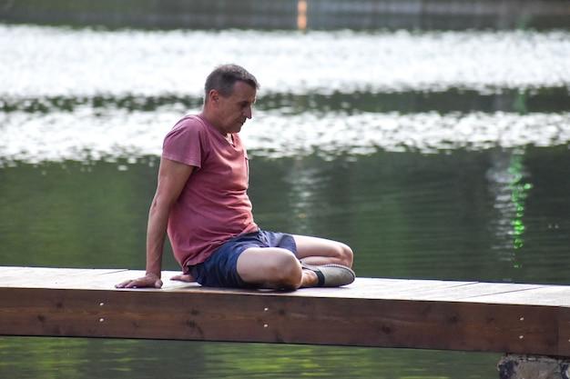 Homme d'âge moyen faisant des asanas de yoga. un athlète masculin s'entraîne sur la jetée à l'extérieur dans le parc d'été.