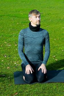 Homme d'âge moyen faisant la respiration, la relaxation, le yoga, les étirements, l'exercice, l'entraînement dans le parc à l'aide d'un tapis de yoga. yoga pour débutant naturel posant. concept de soins de santé.
