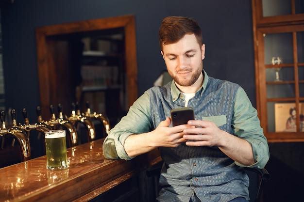 Un homme d'âge moyen. guy avec un téléphone au bar. homme en chemise en jean dans une cellule.