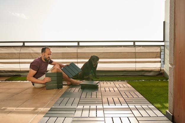 Homme d'âge moyen installant un sol artificiel sur sa terrasse avec son labrador retriever assis à côté de lui