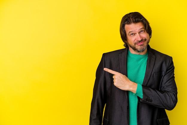 Homme d'âge moyen isolé sur mur jaune souriant et pointant de côté, montrant quelque chose à l'espace vide