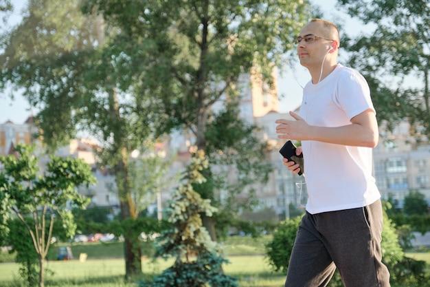 Homme d'âge moyen avec des lunettes traverse le parc de la ville avec un casque
