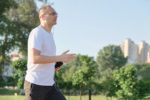 Homme d'âge moyen avec des lunettes traverse le parc de la ville avec des écouteurs