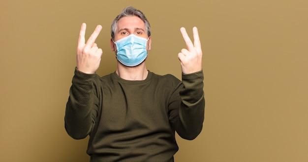 Homme d'âge moyen avec un masque de protection, faisant des signes de paix