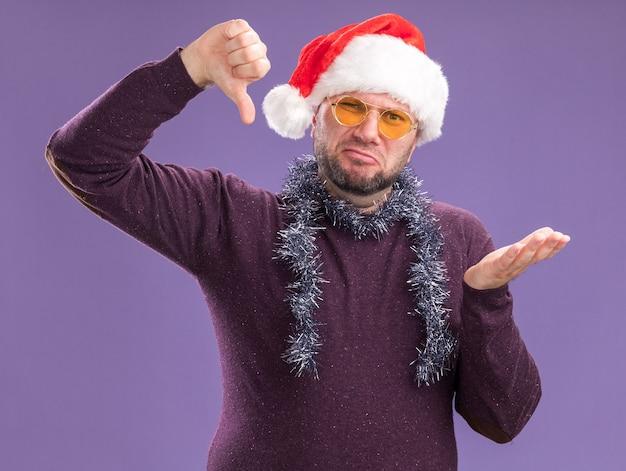 Homme d'âge moyen mécontent portant bonnet de noel et guirlande de guirlandes autour du cou avec des lunettes montrant la main vide et le pouce vers le bas isolé sur mur violet