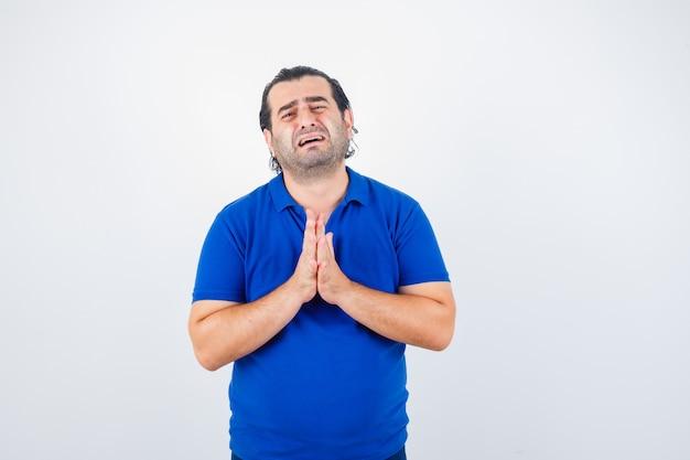 Homme d'âge moyen montrant les mains jointes en geste de plaidoirie en t-shirt bleu et à l'espoir, vue de face.