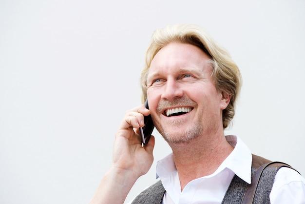 Homme d'âge moyen parlant au téléphone mobile contre un mur blanc