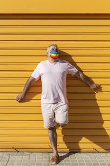 Homme d'âge moyen portant un chapeau, des lunettes de soleil et un masque de protection de couleur arc-en-ciel. lgtb sur fond jaune. concept covid-19