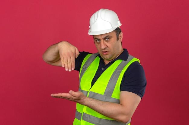 Homme d'âge moyen portant gilet jaune de construction et casque de sécurité guidant quelqu'un vers la direction gesticulant avec les mains à la confiance sur mur rose isolé