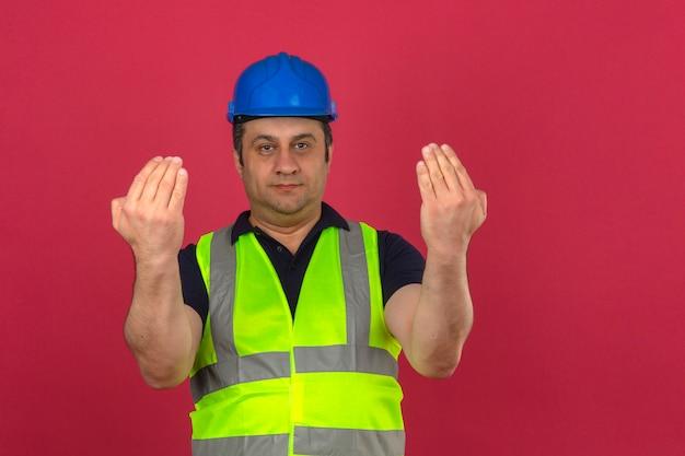 Homme d'âge moyen portant gilet jaune de construction et casque de sécurité guidant quelqu'un vers la direction sur mur rose isolé