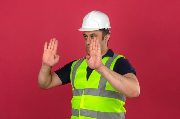 Homme d'âge moyen portant gilet jaune de construction et casque de sécurité guidant quelqu'un vers le geste d'arrêt de direction sur mur rose isolé
