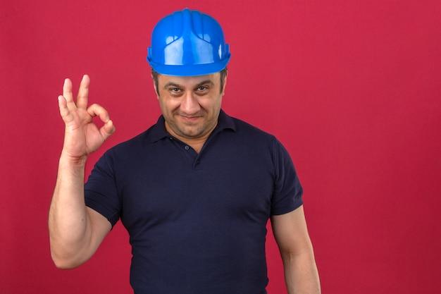 Homme d'âge moyen portant polo et casque de sécurité faisant signe ok avec sourire sur le visage sur mur rose isolé