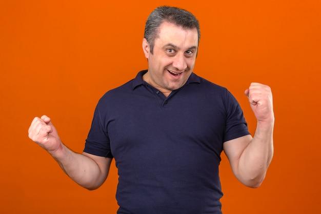 Homme d'âge moyen portant un polo souriant levant les poings comme un gagnant sur mur orange isolé