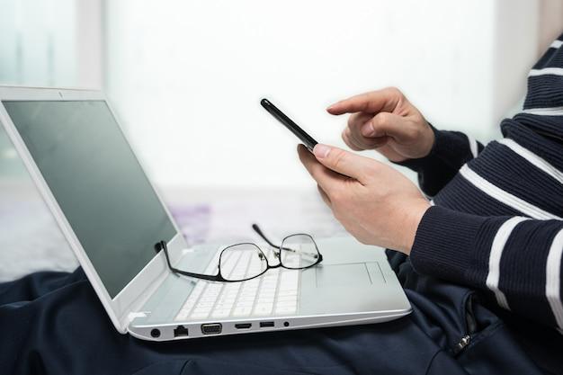 Un homme d'âge moyen qui est habillé de façon décontractée à la maison et travaille à domicile à l'aide d'un ordinateur.