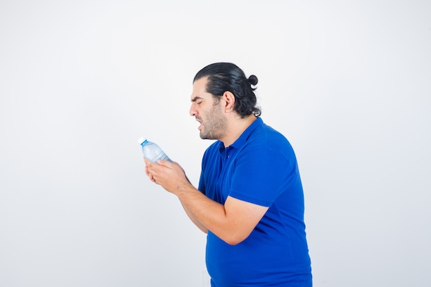 Homme d'âge moyen regardant une bouteille d'eau en t-shirt bleu et à la colère. vue de face.