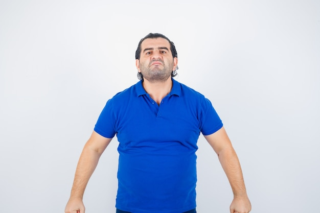 Homme d'âge moyen regardant la caméra en t-shirt bleu et à la recherche de sérieux. vue de face.