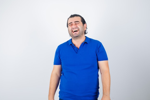 Homme d'âge moyen riant en t-shirt bleu et à la vue de face, joyeuse.