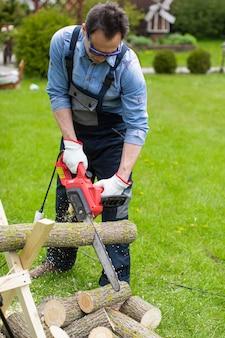 Un homme d'âge moyen en salopette coupe un tronc de tremble en morceaux avec une tronçonneuse