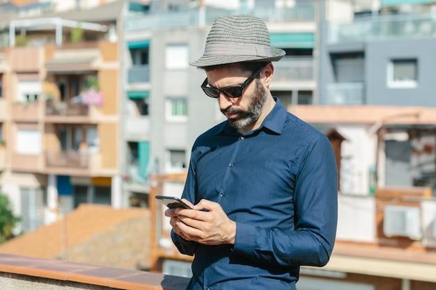 Homme d'âge moyen séduisant avec chapeau et lunettes de soleil discutant avec un téléphone intelligent debout sur un balcon.