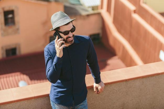 Homme d'âge moyen séduisant avec chapeau et lunettes de soleil parlant à un téléphone intelligent debout sur un balcon.