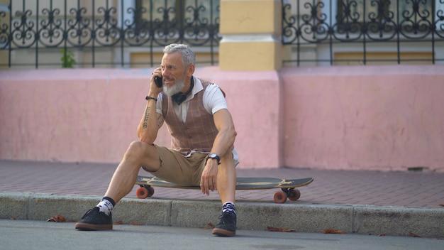 Homme d'âge moyen séduisant parle sur mobile assis sur une planche à roulettes sur le trottoir de la rue