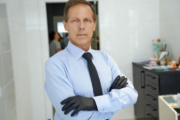 Homme d'âge moyen sérieux dans des gants debout crossarmed