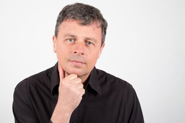 Homme d'âge moyen sérieux avec la main sur le menton
