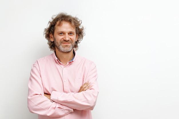 Homme d'âge moyen souriant aux cheveux bouclés sur fond blanc