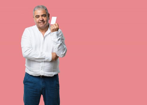 Homme d'âge moyen souriant confiant, offrant une carte de visite, a une entreprise prospère