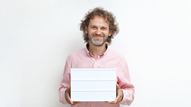 Homme d'âge moyen souriant drôle avec des cheveux bouclés et une boîte à lumière dans ses mains pour l'espace de copie
