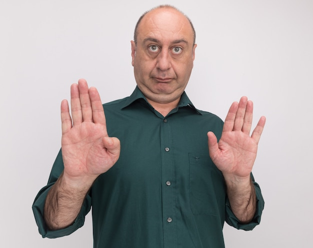 Homme d'âge moyen strict portant un t-shirt vert montrant un geste d'arrêt isolé sur un mur blanc