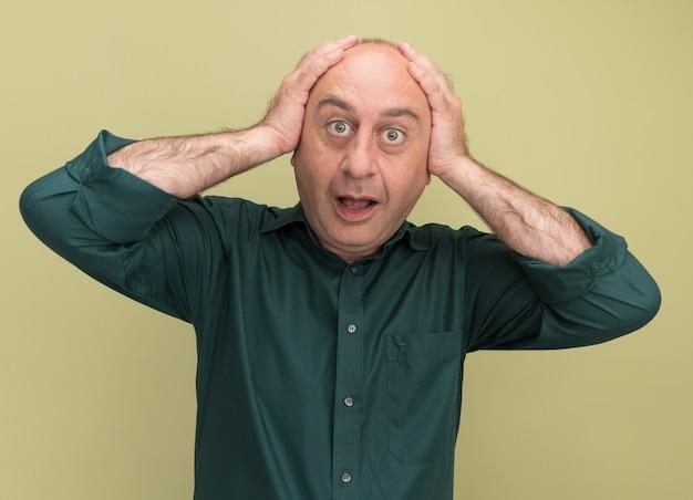 Un homme d'âge moyen surpris portant un t-shirt vert a saisi la tête isolée sur un mur vert olive