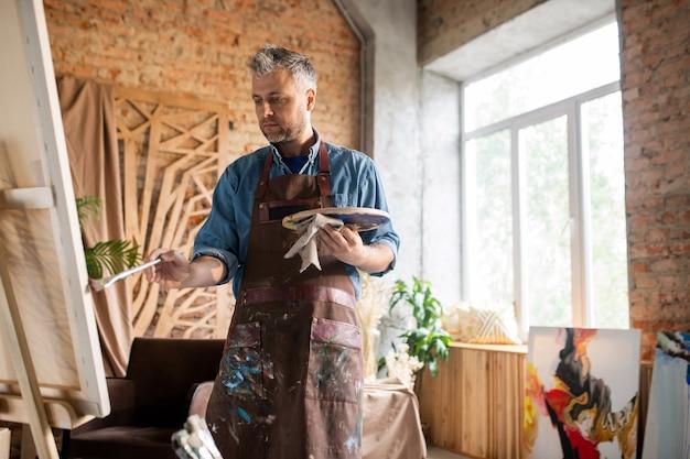 Homme d'âge moyen en tablier à la peinture sur chevalet tout en travaillant en studio d'art ou atelier