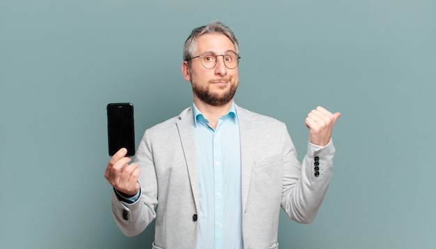 Homme d'âge moyen tenant un smartphone