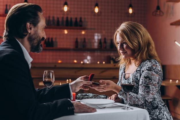 Homme d'âge moyen tend la boîte avec la bague de mariage à une femme surprise
