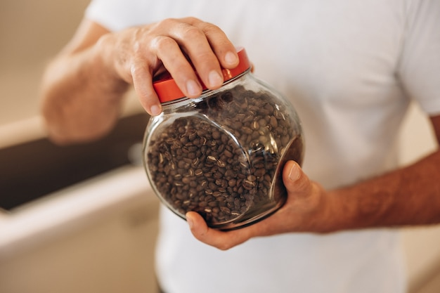 L'homme d'âge moyen tient un pot de grains de café