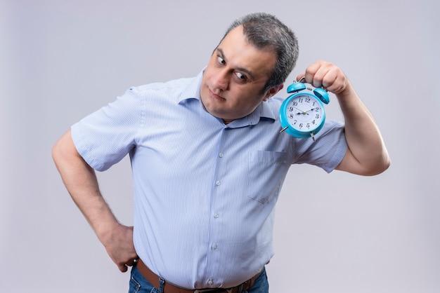 Homme d'âge moyen vêtu d'une chemise à rayures verticales bleu à l'écoute de l'horloge son tic-tac tenant un réveil bleu sur fond blanc