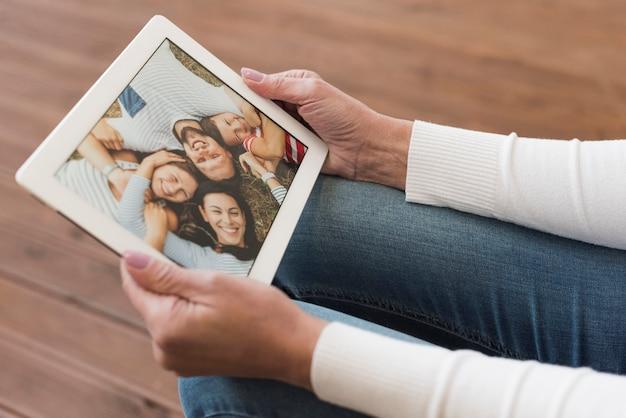 Homme d'âge mûr à angle élevé à la recherche de photos avec ses enfants et petits-enfants