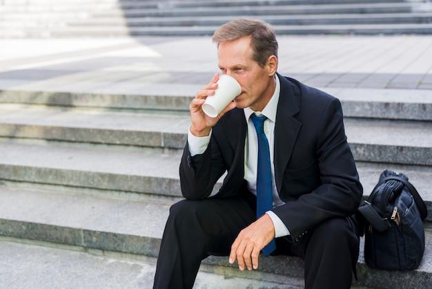 Homme d'âge mûr assis sur un escalier en buvant du café
