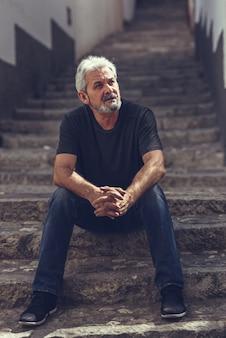 Homme d'âge mûr assis sur des marches en milieu urbain