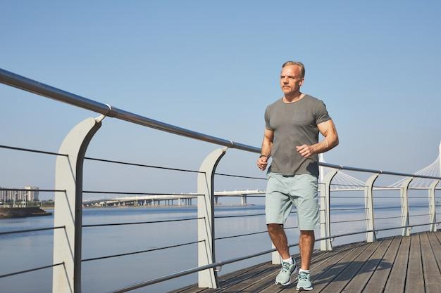 Homme d'âge mûr athlétique en short jogging sur le remblai de la ville le matin, concept de mode de vie sain