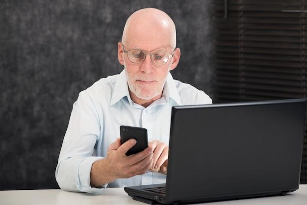 Homme d'âge mûr avec une barbe et une chemise bleue au bureau