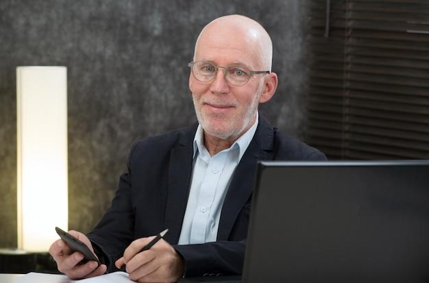 Homme d'âge mûr avec une barbe et une veste bleue au bureau